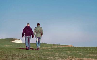 male couple holding hands on a hill.