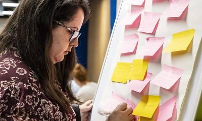 Woman writing on a Post-It board