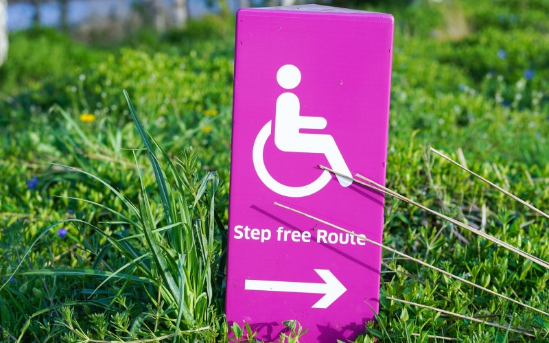 Pink step free access sign on grass