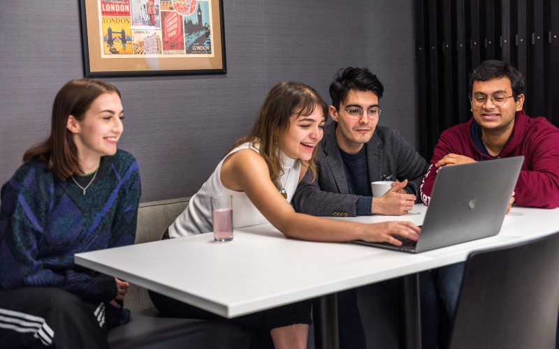 UCL students gathered around a laptop