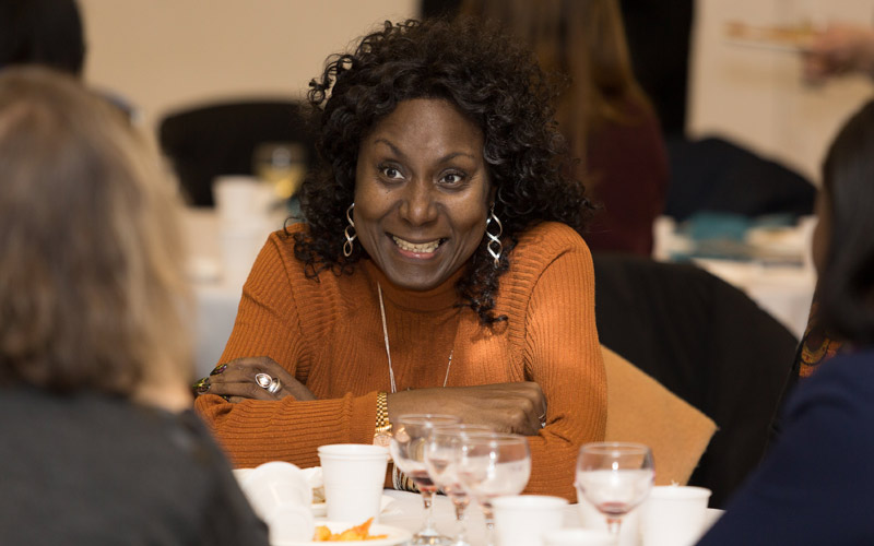 A smiling woman with folded arms at a UCL Alumni event