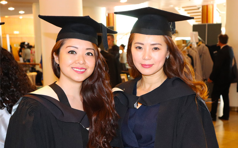 UCL Alumni: Two women wearing mortarboard academic caps attend a graduation ceremony
