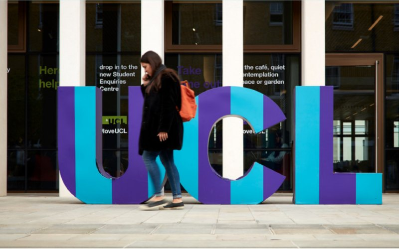 Student walking in front of a UCL display