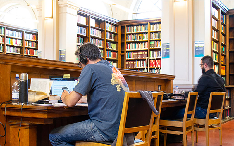 UCL Alumni: A man studies in a library while wearing headphones