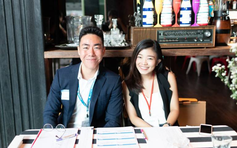 Two alumni sitting at a desk smiling for the camera