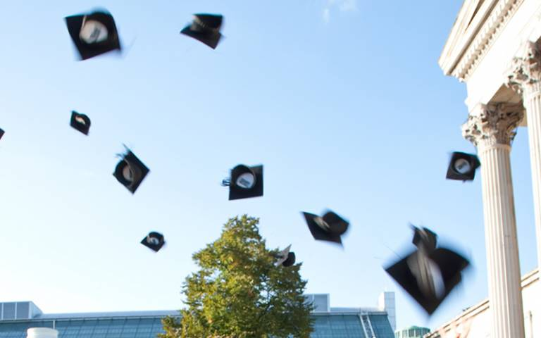 Mortarboards thrown in the air in front of the Wilkins Building