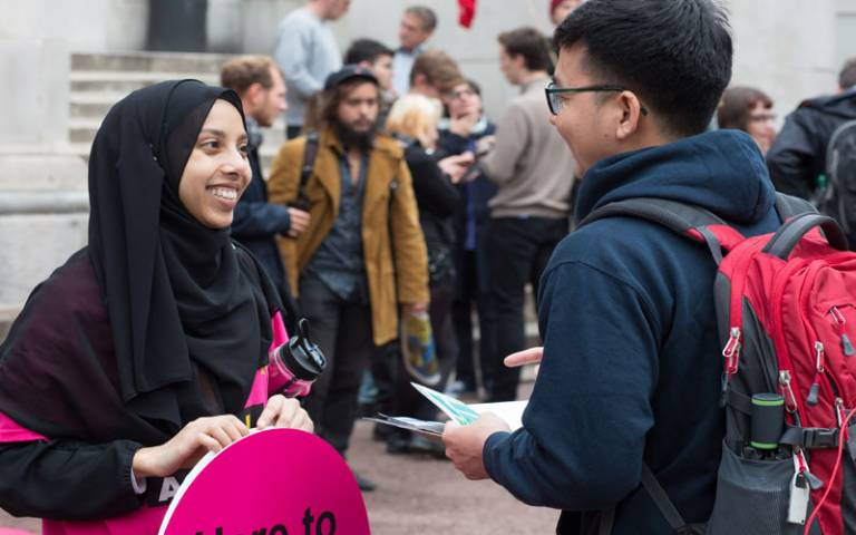A UCL volunteer chats to a fellow student at an event