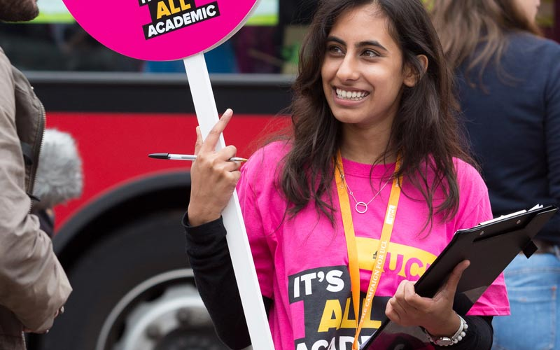 A woman holding a pink sign volunteers a a UCL alumni event