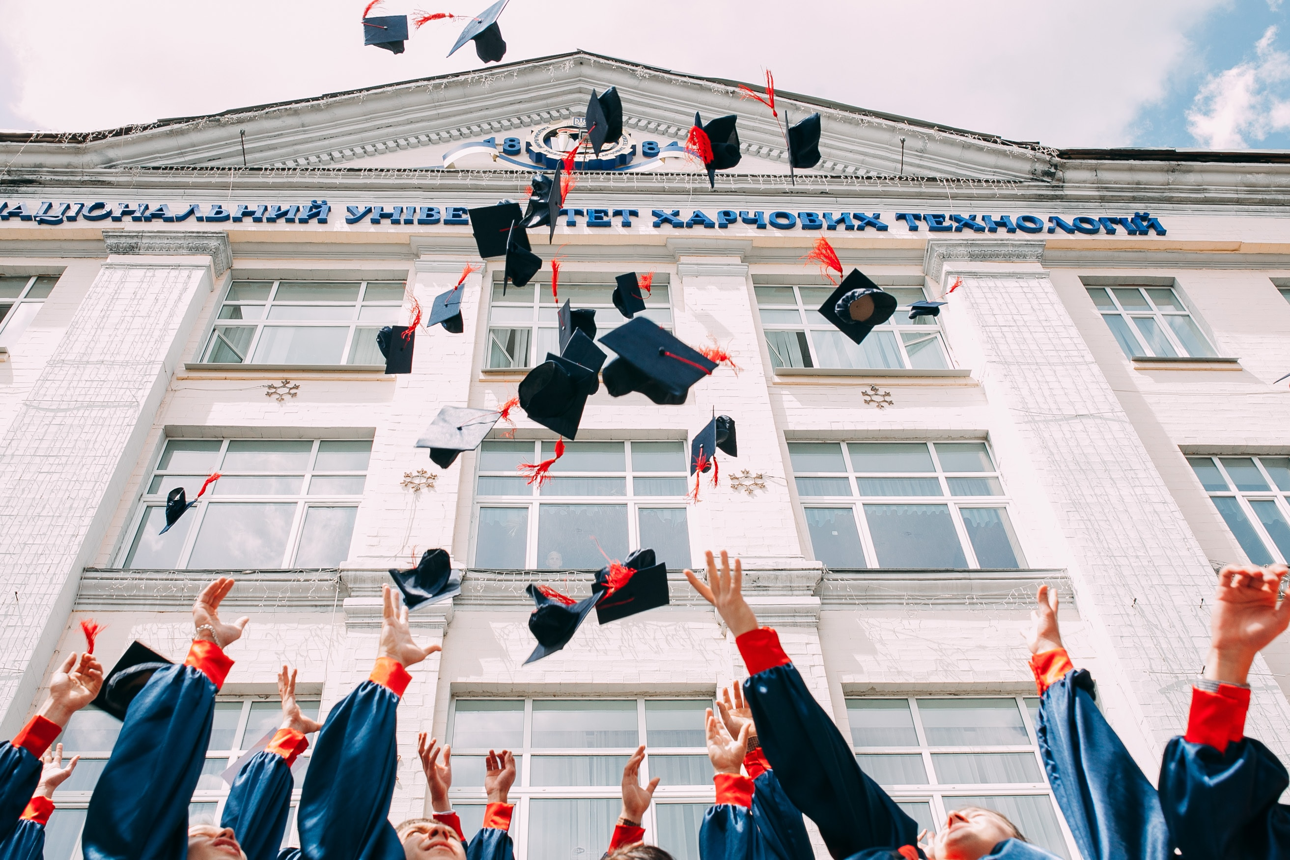 Students throwing mortarboards in the air