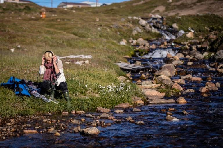 Artist Kat Austen doing fieldwork in headphones, beside water