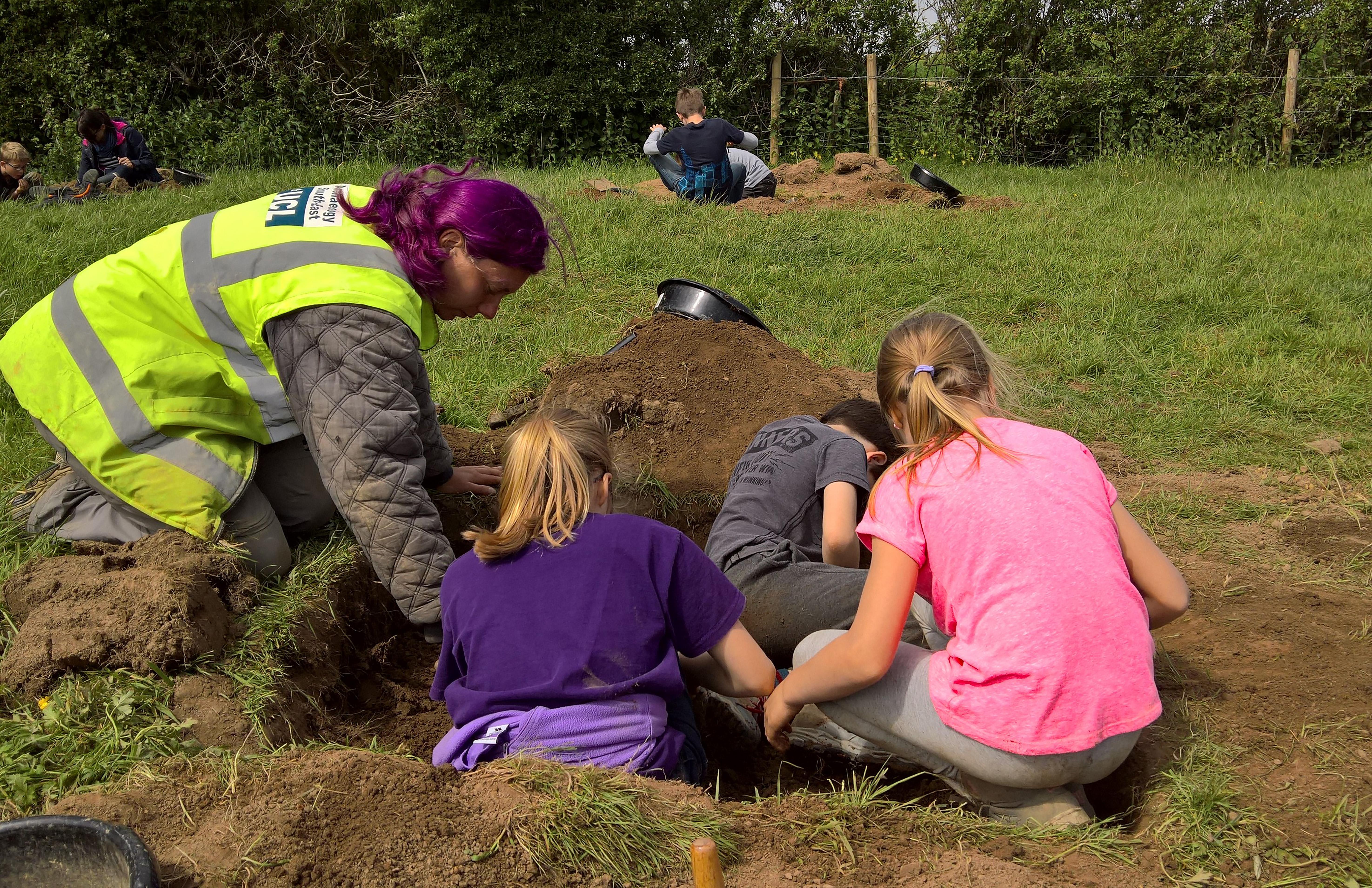 An archaeologist helps children excavate