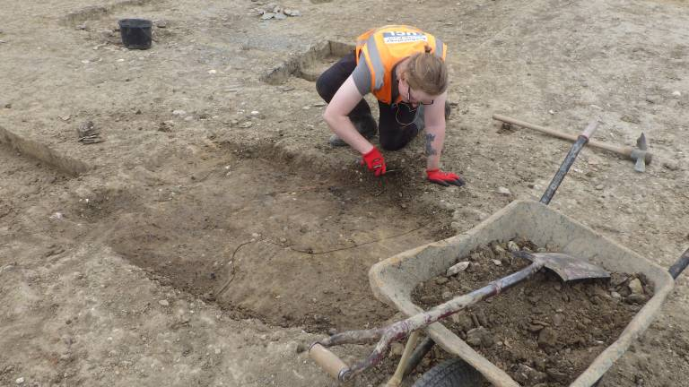 Alex excavating on site behind a wheelbarrow in the foreground. He wears glasses and has tied his mid-length blonde hair in a bun.