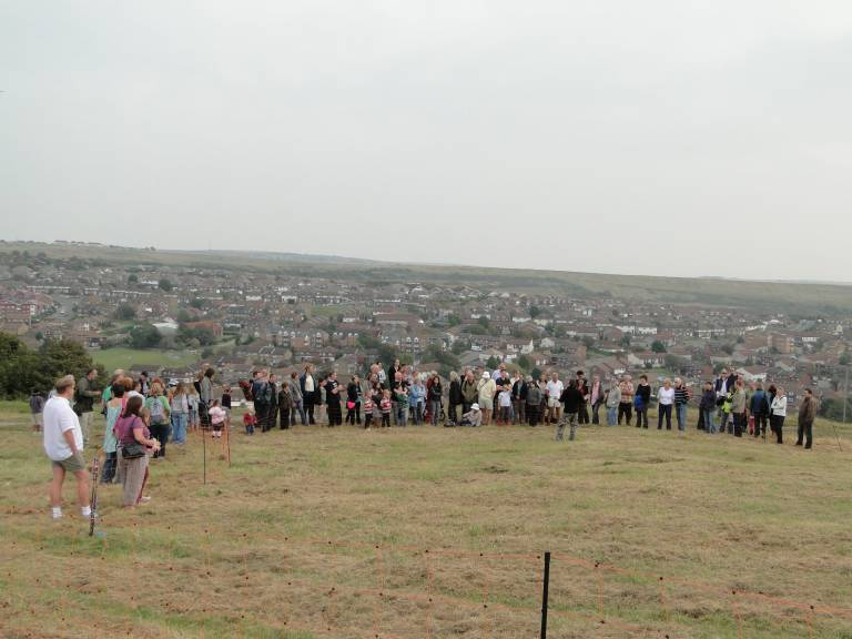 A crowd of people stand on a hill top rising above houses, listening to one person speaking.