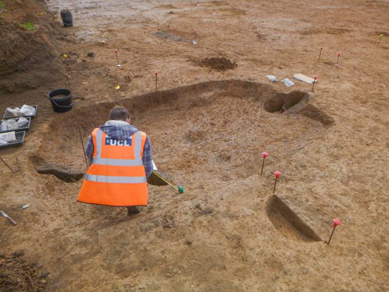 An archaeologist works inside the remains of a sunken featured building. The ovoid rectangular depression is about 4m by 2m in size, and in the middle of each short edge a posthole has been found. The archaeologist has their back to us.
