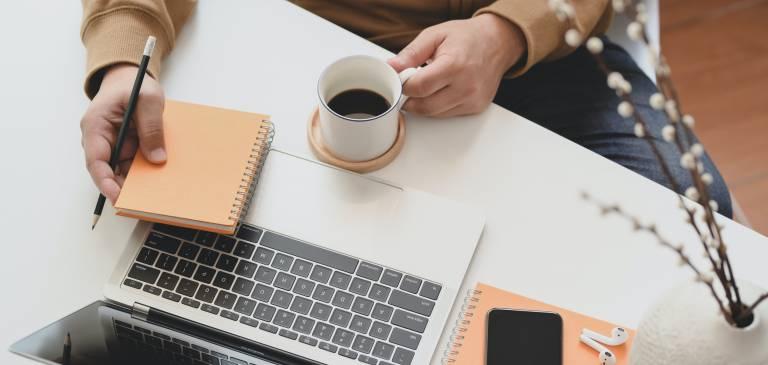 person-holding-white-ceramic-mug-beside-macbook-pro