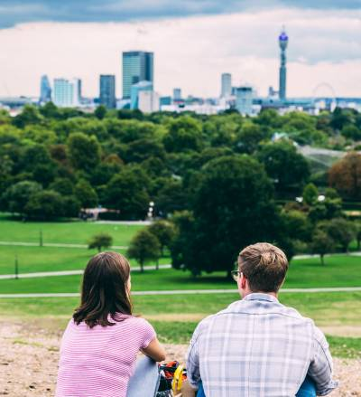 Two people sitting on Primrose Hill looking at the London skyline