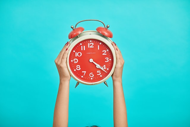 two hands holding a red alarm clock