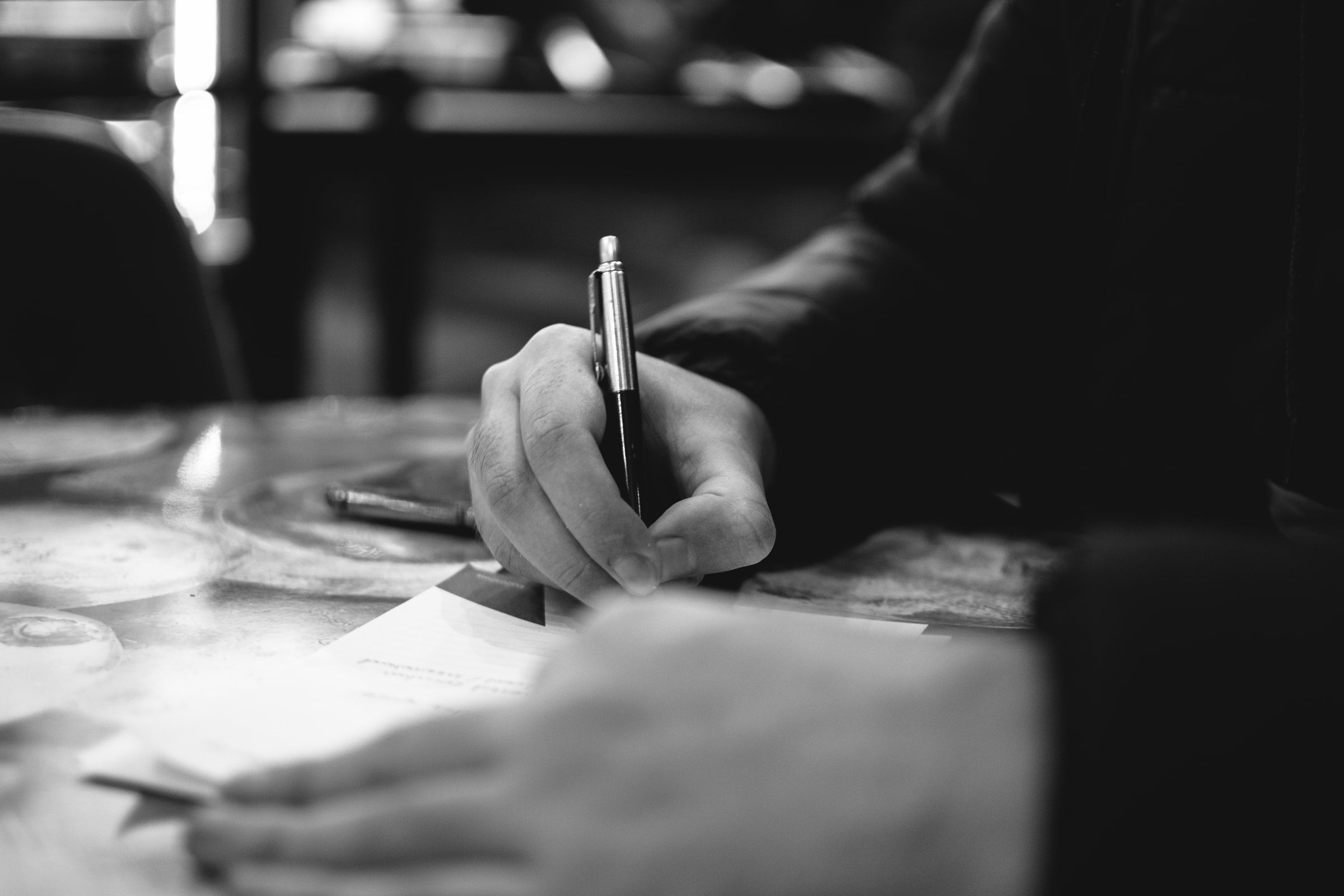 Black and white photo of hand writing on paper