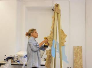 Woman painting on a wooden easle