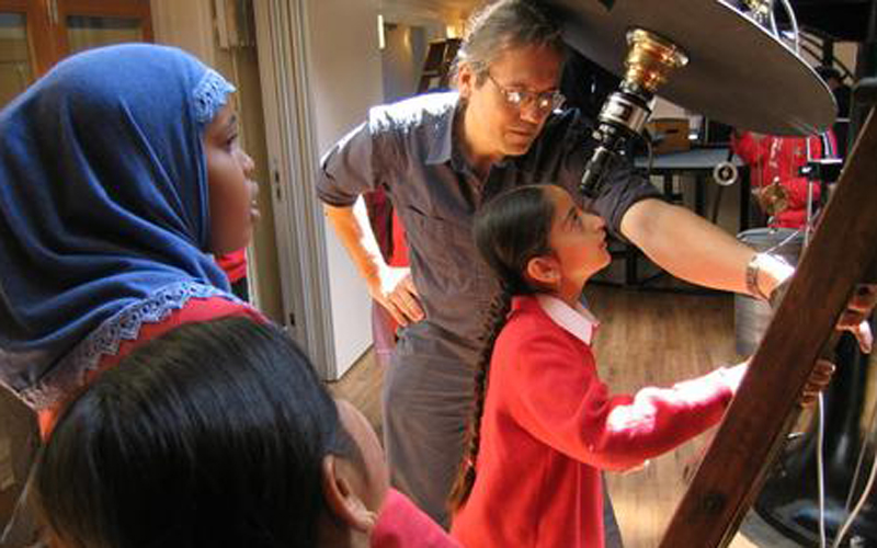 Observatory IT manager Theo Schlichter assists school children observing the Sun through a narrow band hydrogen filter.