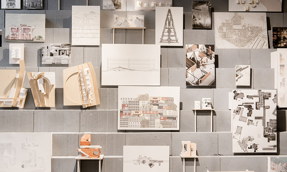 Three shelves with drawings and objects of architecture and buildings