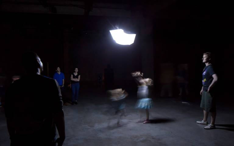A bright light on the ceiling in a pitch black room with people below blurred through movement
