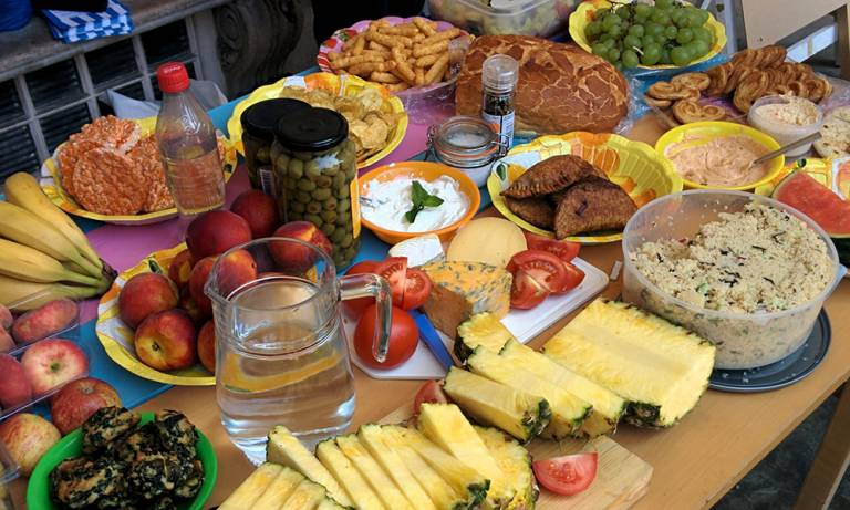 A table of snack food, fruits and vegetables.