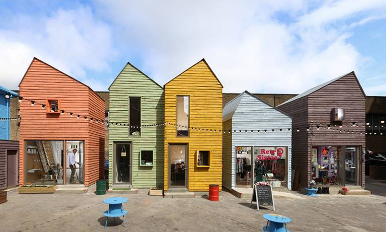 A row of buildings styled as brightly coloured beach houses