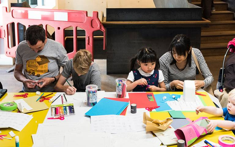 The Bartlett Summer Show Family Day 2018. Two children and their parents are sitting at a table doing arts and crafts.