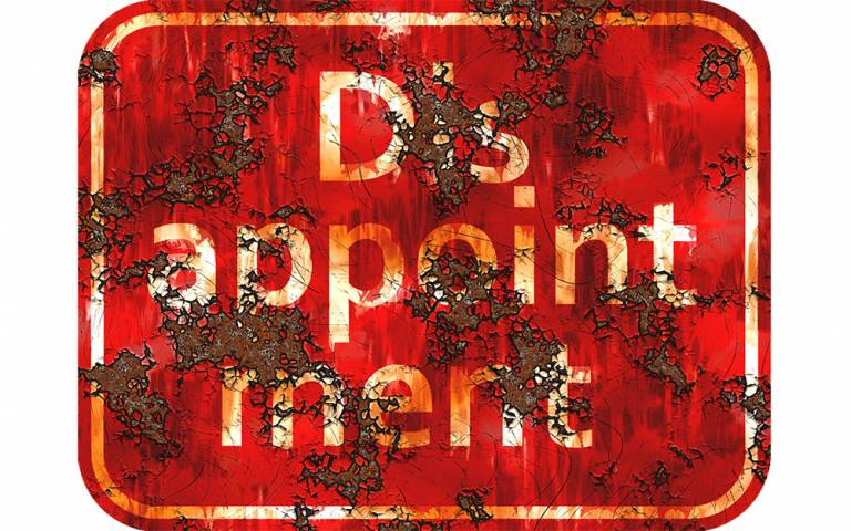 Rusty red sign with white text reading 'disappointment'