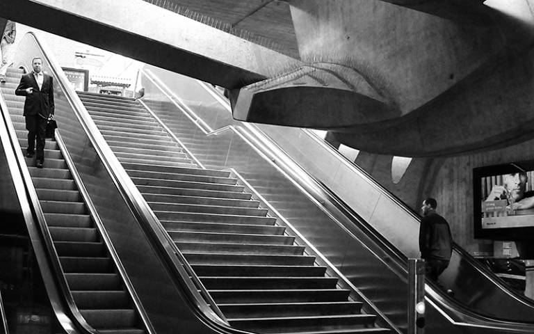 Black and white photograph of two men going up and down escalators in opposite directions