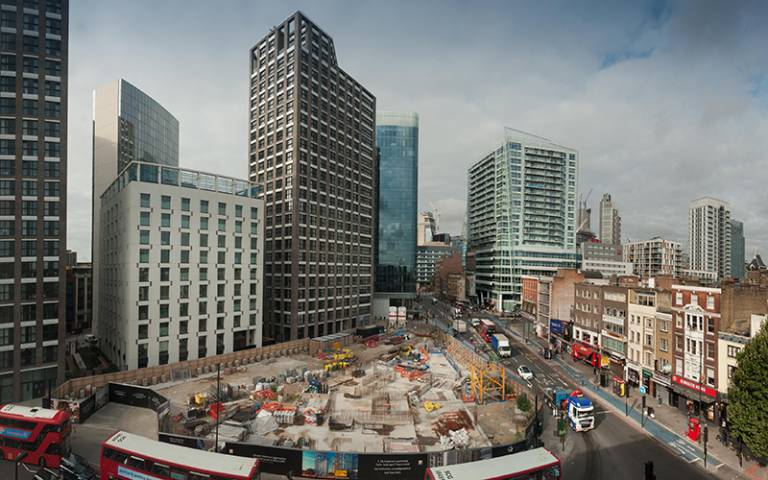 Buses drive around a building site surrounded by tall buildings in Whitechapel