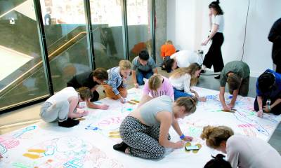 young people drawing maps on a large piece of paper on the floor