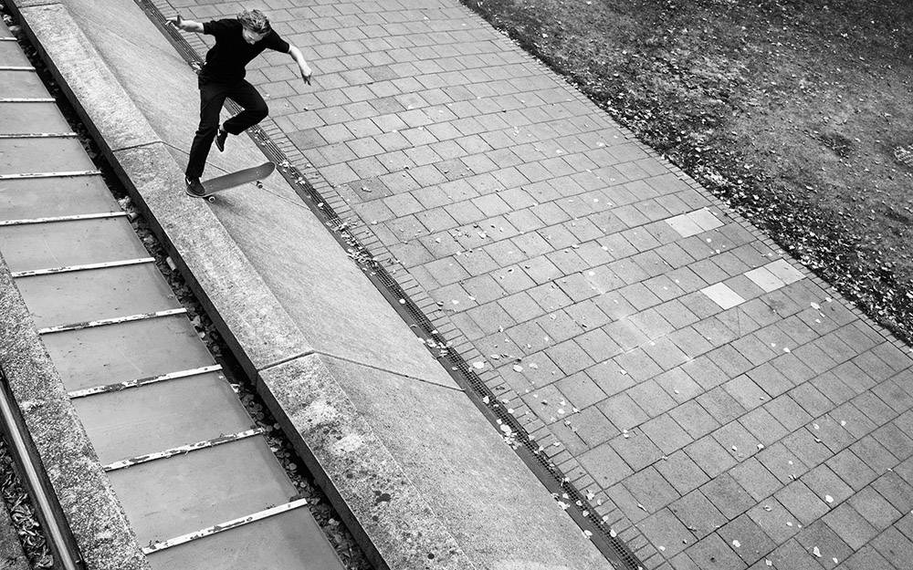 black and white photo of man skateboarding