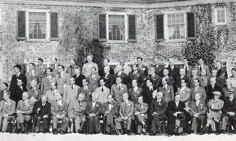 Black and white image of men in suits posing for a photograph