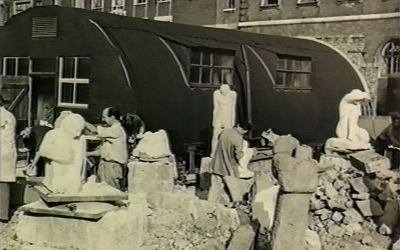 """Sculpture students carving bomb debris in East London"". Still from an unidentified film. London Metropolitan University Archives."