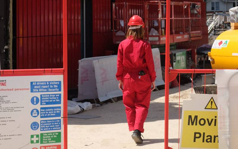 Attending Spaces, by Elin Eyborg Lund. A person in red construction gear, walking away from the camera, through a construction site.