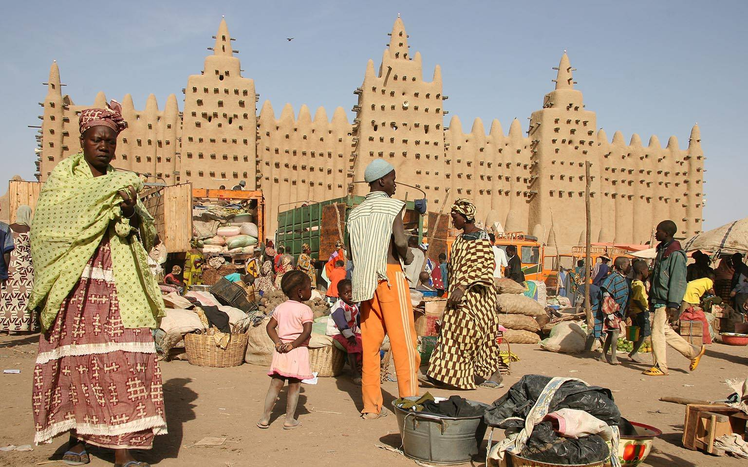 Mosque in Djenne with families in a market place in the foreground