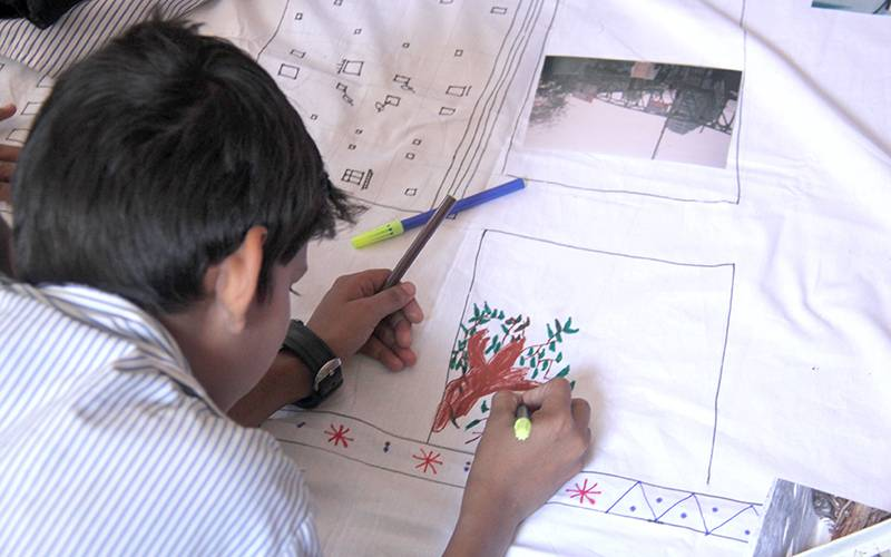 A child draws on fabric in his school in Mumbai