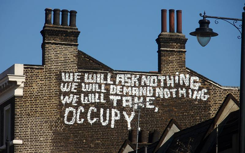 'We will ask nothing, demand nothing, we will take, occupy' painted in white on a brick building