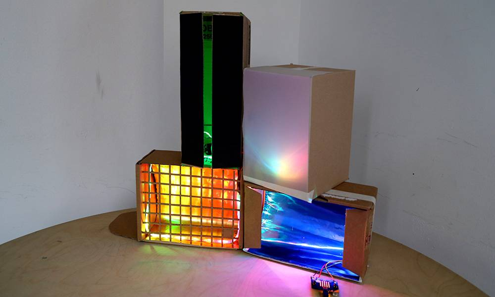 cardboard boxes cut out with coloured lights inside