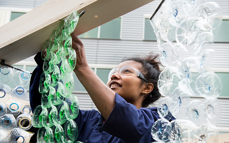 A female student hangs an installation made of parts of plastic bottles