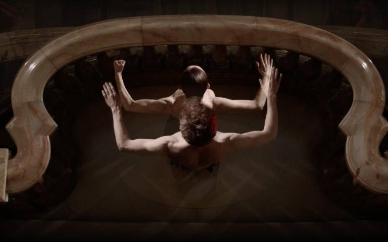 Arial view of a male dancer stood behind a female dancer on a marble balcony. They are two images placed on top of each other.