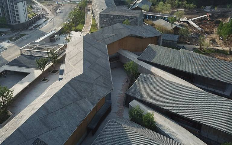 Roof tops of buildings which zig zag across the landscape