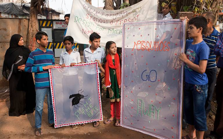 Mumbai students stand outside with their anti-mosquito banners