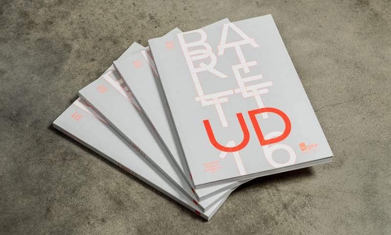 A stack of MArch UD 2016 books on a concrete floor