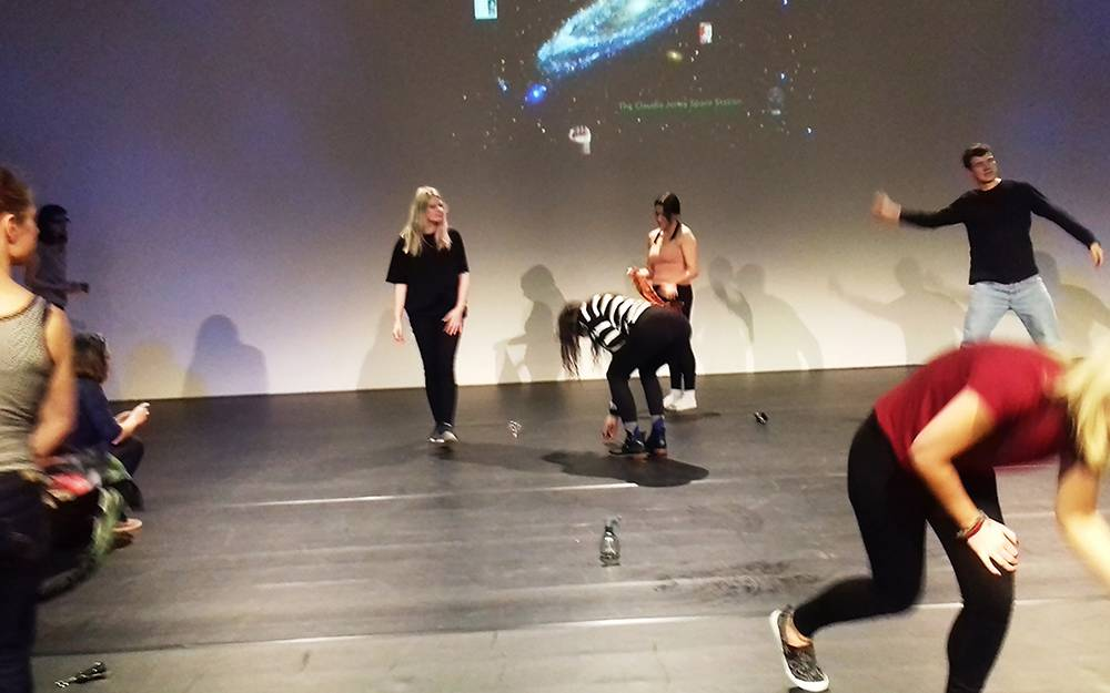 People performing in front of a screen showing the earth and space