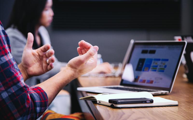 Hands gesticulating in front of computer screens