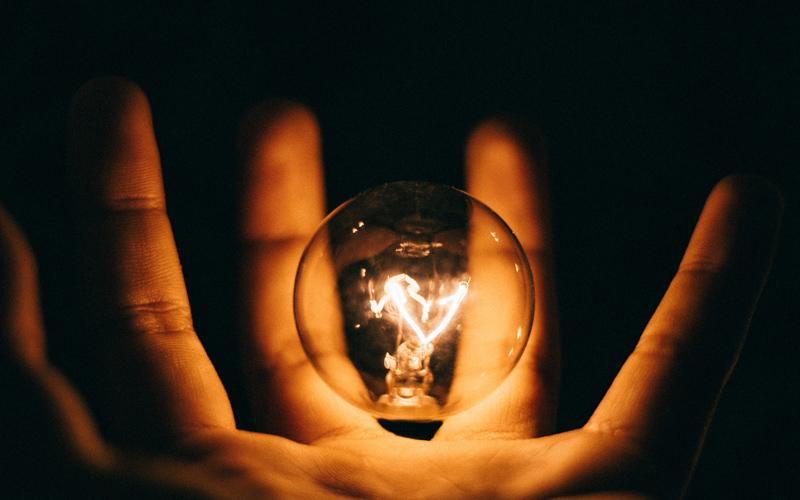 Hand clutching a light bulb