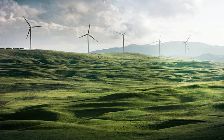 Photo shows a green hilly field with wind turbines in the background against a cloudy sky.